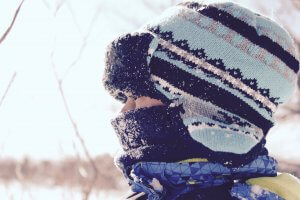 A young boy with a winter hat and scarf on