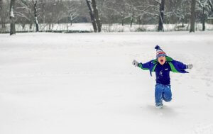 Excited young boy running in the snow