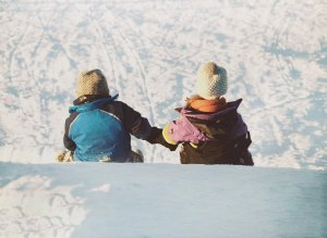 A boy and girl sledding in the winter